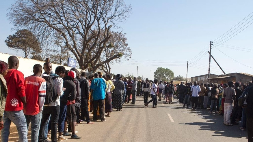 Zambians queue to cast their votes at a polling station in Lusaka, Thursday, Aug. 11, 2016, in a tight election race for president and parliament in the democratic nation.  The election campaign has been marred by violence between rival factions, but there are no early reports of unrest during voting. (AP Photo/Moses Mwape)