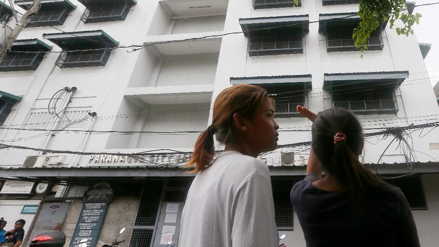 A relative waves to check the condition of a prisoner hours after officials said numbers of inmates, including alleged Chinese drug criminals, died in a suspected grenade blast at the Paranaque City Jail Friday, Aug. 12, 2016, in suburban Paranaque city, south of Manila, Philippines. The warden was seriously injured in Thursday night's explosion. (AP Photo/Bullit Marquez)