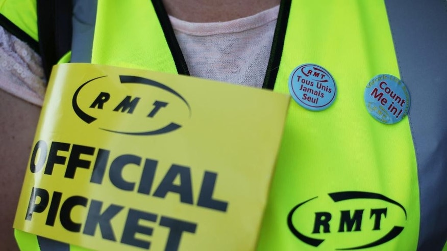 A union member joins a picket line outside St. Pancras International train station in London, as Eurostar workers begin a four-day strike, Friday Aug. 12, 2016.  Dozens of train managers on Eurostar services traveling under the English Channel to France, have walked off the job in a dispute over working conditions, although the company predicts the strike will have only limited effect on its schedule. (Yui Mok / PA via AP)
