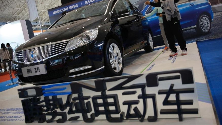 FILE - In this April26, 2016 file photo, visitors examine a Chinese automaker Denza electric vehicle on display at the Beijing International Automotive Exhibition in Beijing. China's auto sales growth accelerated in July, an industry group said Friday, Aug. 12, while General Motors Co. and Ford Motor Co. reported record demand for the month. Sales in the world's biggest auto market rose 26.3 percent to 1.6 million units, the China Association of Automobile Manufacturers said. (AP Photo/Andy Wong, File)