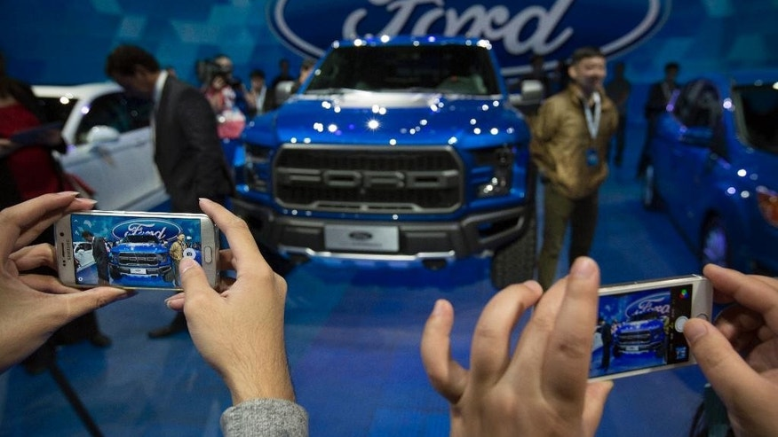 FILE - In this April 23, 2016 file photo, attendees take photos of a Ford F-150 Raptor pickup truck by smart phones at a promotional event for Ford ahead of the biennial Auto China car show in Beijing. China's auto sales growth accelerated in July, an industry group said Friday, Aug. 12, while General Motors Co. and Ford Motor Co. reported record demand for the month. Sales in the world's biggest auto market rose 26.3 percent to 1.6 million units, the China Association of Automobile Manufacturers said. (AP Photo/Mark Schiefelbein, File)