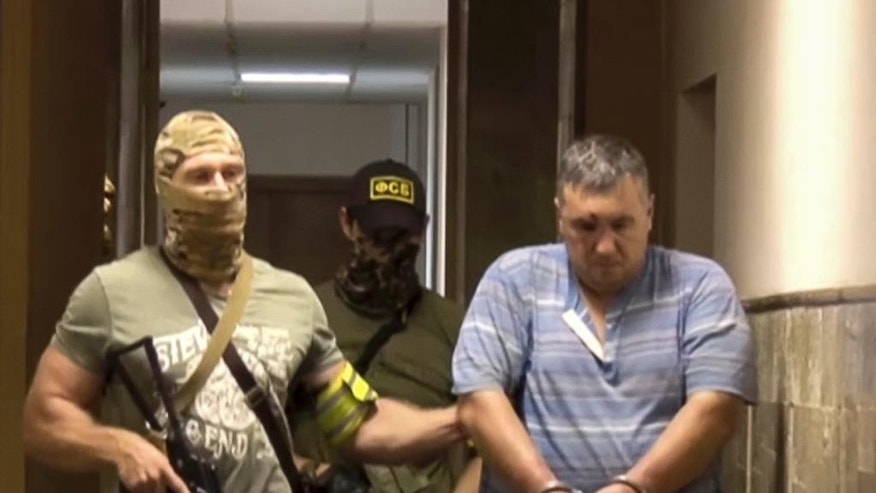 In this grab taken from a footage provided by Russian Federal Security Service Press Service, a handcuffed man identified as Yevgeny Panov, suspected of being involved in a group that Russia's Federal Security Service (FSB) identified as Ukrainian 'saboteurs,' is led by FSB officers in Crimea, on Thursday, Aug. 11, 2016. The FSB said its agents thwarted an attempt by Ukrainian 'saboteurs' to conduct terror attacks in Crimea. Ukraine has denied the claim. (Russian Federal Security Service Press Service via AP)