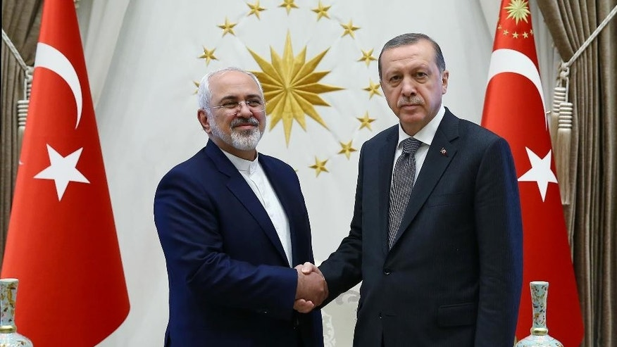 Turkish President Recep Tayyip Erdogan, right, shake hands with the Iranian Foreign Minister Mohammad Javad Zarif, during their meeting in Ankara, Friday, Aug. 12, 2016. Turkey and Iran have held opposing positions on Syria, with Iran backing the government of Syrian President Bashar Assad and Turkey advocating his departure. (Kayan Ozer/Presidential Press Service via AP)