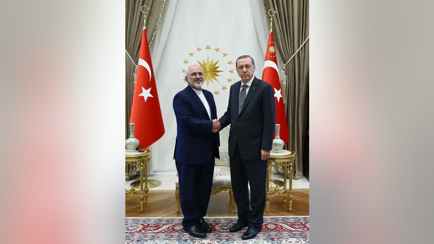 Turkish President Recep Tayyip Erdogan, right, shakes hands with the Iranian Foreign Minister Mohammad Javad Zarif during their meeting in Ankara, Friday, Aug. 12, 2016.  Turkey and Iran have held opposing positions on Syria, with Iran backing the government of Syrian President Bashar Assad and Turkey advocating his departure. (Kayan Ozer/Presidential Press Service via AP)