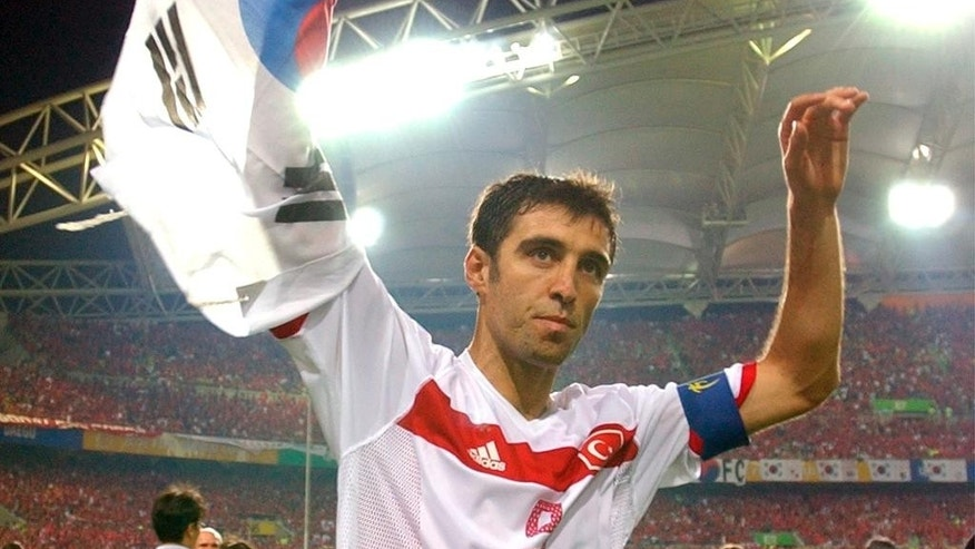 FILE - In this Saturday, June 29, 2002, file photo, Turkey's Hakan Sukur holds a South Korean flag at the end of the 2002 World Cup third place playoff soccer match between South Korea and Turkey, at the Daegu World Cup stadium, in Daegu, South Korea.  Turkey's state-run news agency reports Friday, Aug. 12, 2016, authorities have issued an arrest warrant for former soccer star and legislator Hakan Sukur over his alleged links to a U.S.-based Muslim cleric, accused by Turkey of masterminding last month's failed coup. (AP Photo/Vincent Yu, FILE)