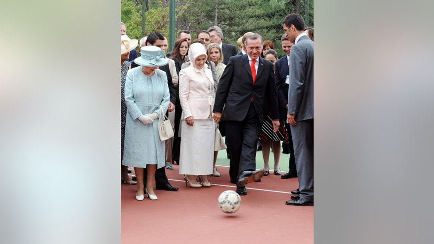 FILE - In this Friday, May 16, 2008, file photo Britain's Queen Elizabeth II, left, with Turkish Prime Minister Tayyip Erdogan, 2nd right, and his wife Emine Erdogan, second left, and Turkish soccer star Hakan Sukur, right, during a garden party at the British Embassy in Ankara. Turkey's state-run news agency reports Friday, Aug. 12, 2016  authorities have issued an arrest warrant for former soccer star and legislator Hakan Sukur over his alleged links to a U.S.-based Muslim cleric who is accused by Turkey of masterminding last month's failed coup. (AP Photo/Firat Yurdakul, Pool, File)
