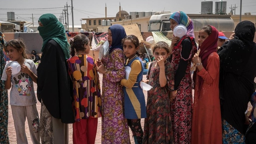 FILE - In this Aug. 7, 2016 file photo, women and children stand in line to receive a portion of food at Dibaga camp for internally displaced civilians in Iraq. The U.N. refugee agency says that more than 100,000 people have been displaced as Iraqi forces clear territory ahead of the critical battle for the Islamic State-held city of Mosul. (AP Photos/Alice Martins)