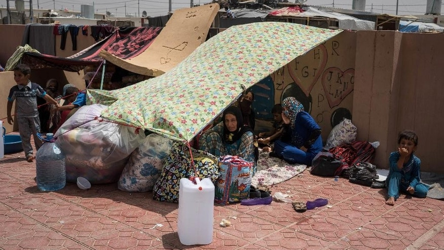 FILE - In this Aug. 7, 2016 file photo, women and children rest under an improvised tent in a yard where they have been sleeping at Dibaga camp for internally displaced civilians in Iraq. The U.N. refugee agency says that more than 100,000 people have been displaced as Iraqi forces clear territory ahead of the critical battle for the Islamic State-held city of Mosul.(AP Photo/Alice Martins, File)