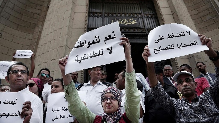 "Egyptians protest against the latest surge of assaults on Christians in Cairo, Egypt, Saturday, Aug. 13, 2016. Egyptian Christians have staged a rare protest in downtown Cairo to demand the government uphold their rights, saying they are sorely lacking and they are treated as second-class citizens in the Muslim-majority country. Arabic on the sign at right reads, ""no to pressure on victims for reconciliation,"" at center, ""yes to nationalism and no to extremism."" (AP Photo/Nariman El-Mofty)"