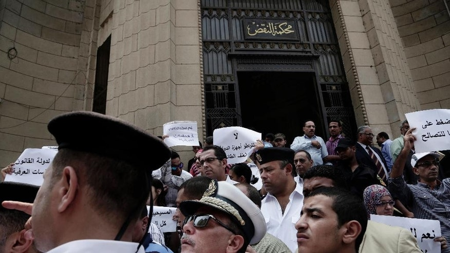 Egyptian police try to break up a protest against the latest surge of assaults on Christians in Cairo, Egypt, Saturday, Aug. 13, 2016. Egyptian Christians have staged a rare protest in downtown Cairo to demand the government uphold their rights, saying they are sorely lacking and they are treated as second-class citizens in the Muslim-majority country. (AP Photo/Nariman El-Mofty)