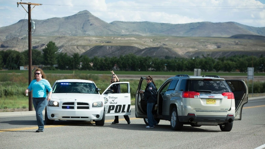 Police officers prevent drivers from entering Hatch, N.M., after a shooting on Friday, Aug. 12, 2016.