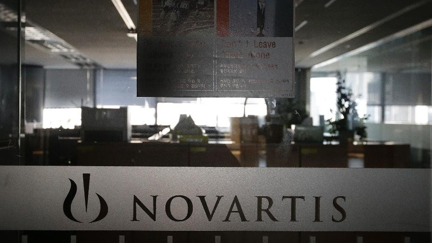 A logo of Swiss pharmaceutical company Novartis is seen at the Novartis Korea office in Seoul, South Korea, Saturday, Aug. 13, 2016. Prosecutors indicted the former chief executive of the South Korean unit of Novartis and five other former and current managers over allegations they illegally paid doctors 2.6 billion won ($2.3 million) in return for prescribing the company's drugs. (AP Photo/Ahn Young-joon)