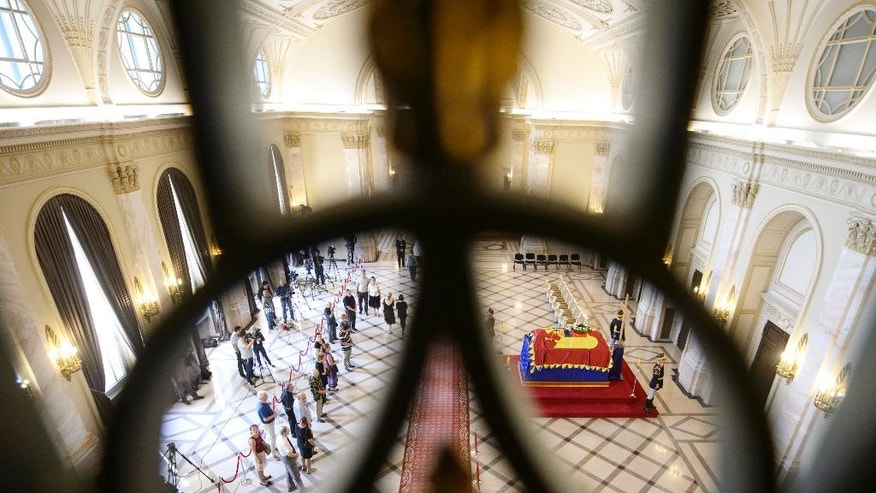 Mourners stand in line to pay their last respects at the flag-draped coffin of Anne of Romania, wife of Romania's last monarch, King Michael, in the throne room at the former Royal Palace in Bucharest, now the National Museum of Art of Romania, in Bucharest, Thursday, Aug. 11, 2016. Hundreds of mourners have paid their respects to Anne of Romania, wife of former King Michael, lying in state at the Royal Palace in Bucharest. Romanians climbed stairs of the elegant palace to the cappuccino-colored marble room where Anne's coffin was placed, draped with a flag bearing the royal crest and flanked by soldiers. (AP Photo/Andreea Alexandru)