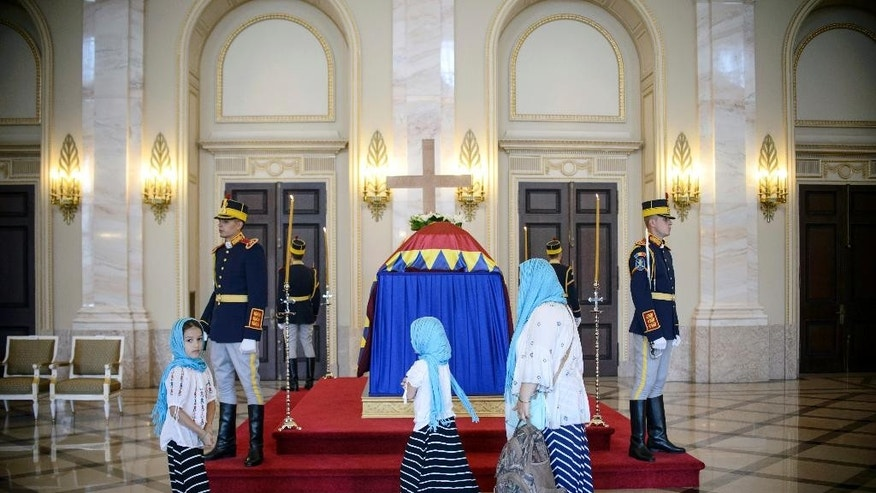 Mourners stand in line to pay their last respects at the flag-draped coffin of Anne of Romania, wife of Romania's last monarch, King Michael, in the throne room at the former Royal Palace, in Bucharest, Thursday, Aug. 11, 2016.  Hundreds of mourners have paid their respects to Anne of Romania, wife of former King Michael, lying in state at the Royal Palace in Bucharest. Romanians climbed stairs of the elegant palace to the cappuccino-colored marble room where Anne's coffin was placed, draped with a flag bearing the royal crest and flanked by soldiers. (AP Photo/Andreea Alexandru)