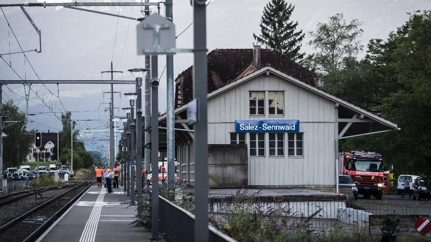 Emergency services attend the scene at Salez - Sennwald train station after a man attacked other passengers aboard a train at Salez, Switzerland, on Saturday, Aug. 13, 2016.  Police in Switzerland say a Swiss man set a fire and stabbed people on a train in the country's northeast, wounding six people some seriously, and injuring himself. (Gian Ehrenzeller / Keystone via AP)