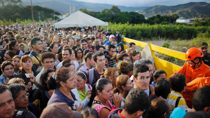 Venezuelans gather to cross the border into Colombia at the Simon Bolivar bridge, Sunday July 17, 2016.