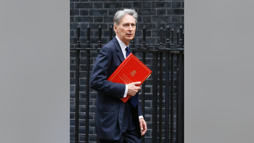 FILE - In this file photo dated Friday, May 13, 2016, Britain's Foreign Secretary Philip Hammond arrives at Downing Street in London.  Britain's Treasury chief Philip Hammond said Saturday Aug. 13, 2016, in a funding guarantee that Britain will keep paying for European Union-funded agriculture, infrastructure and science projects even if Britain leaves the bloc. (AP Photo/Kirsty Wigglesworth, FILE)