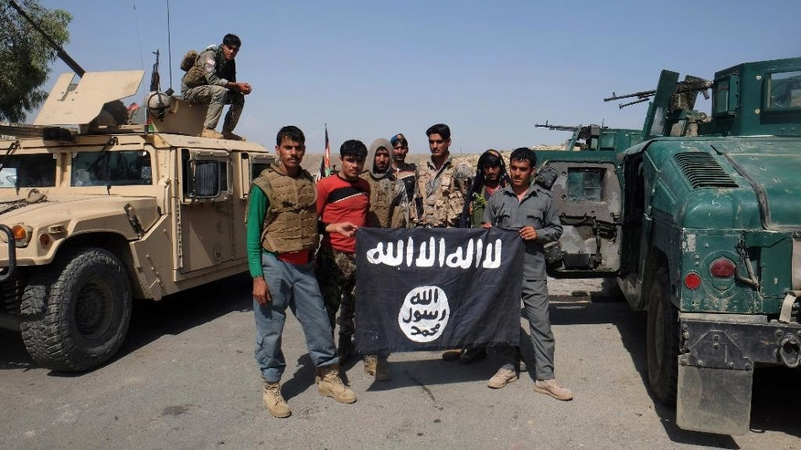 FILE - in this Monday, Aug. 1, 2016 photo, Afghan police pose for a photograph with an Islamic State flag after an operation in the Kot district of Jalalabad province east of Kabul, Afghanistan. The Islamic State group, which has been building a presence in Afghanistan for more than a year, has established a recruitment and training camp in a restive southern province bordering Pakistan. (AP Photo/Melad Hamedi, file)