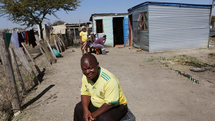 In this Aug. 12, 2016 photo, Ntutuzelo Vukani sits outside his two-room metal shack, in Marikana, South Africa. His shack houses five people and is held together with nails hammered through rusting bottle caps where there is an outdoor tap and a pit latrine toilet. Four years after South African police shot dead 34 mine workers driven to fury by poor living conditions, the British mining company Lonmin has failed to provide the homes it promised for several thousand workers, Amnesty International says. (AP Photo/Denis Farrell)