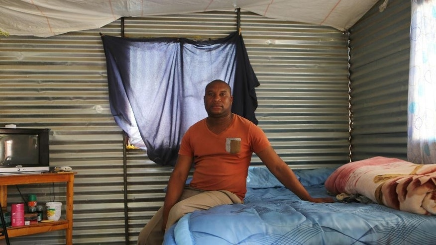 In this Aug. 12, 2016 photo, mine worker Mziseni Zotyatha sits on his bed in his neat, one-room metal shack with plastic sheeting stretched above his bed to keep out the rain, in Marikana, South Africa. Four years after South African police shot dead 34 mine workers driven to fury by poor living conditions, the British mining company Lonmin has failed to provide the homes it promised for several thousand workers, Amnesty International says. (AP Photo/Denis Farrell)