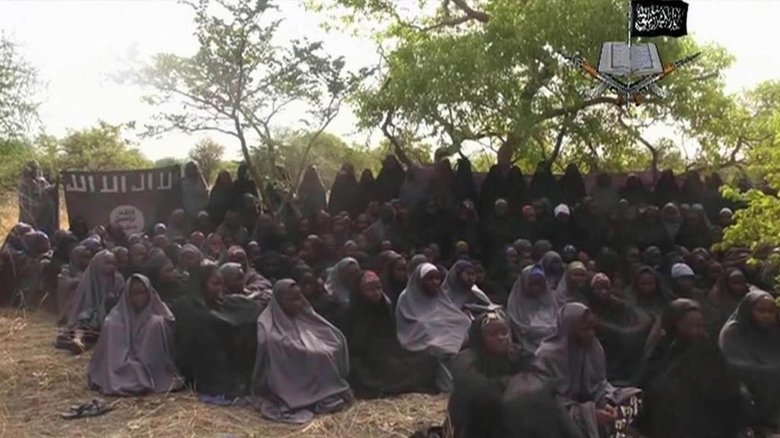 "FILE - This Monday May 12, 2014 file image taken from video by Nigeria's Boko Haram terrorist network, shows the alleged missing girls abducted from the northeastern town of Chibok. A video that appears to be from Boko Haram says some of the abducted Chibok schoolgirls have been killed in Nigerian air strikes and shows one of the alleged victims pleading for authorities to release detained militants so the girls can be freed. The video posted Sunday Aug.14, 2016 on Twitter shows a veiled girl identified as one of the 276 students abducted from a remote school in northeast Nigeria in April 2014, saying some classmates died in aerial bombardments and 40 have been ""married"" to Islamic extremist fighters . (AP Photo/File)"