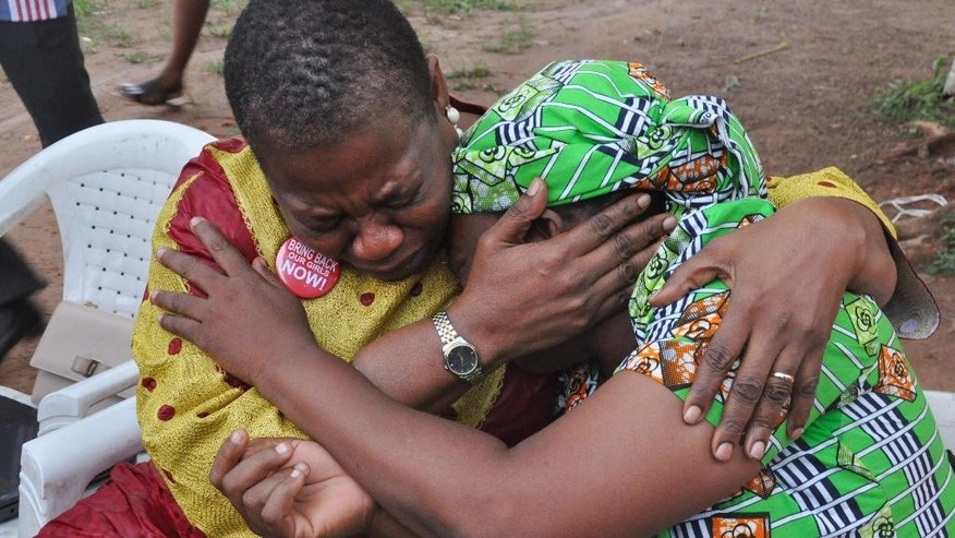 """Bring Back Our Girls"" co-founder Obiageli Ezekwesili, left, console Esther Yakubu, mother of one of the kidnapped school girls, after she saw her daughter in a video release by Boko haram during a briefing in Abuja, Nigeria. Sunday Aug. 14, 2016 . The mother of one of the Chibok girls kidnapped more than two years ago by Nigeria's Islamic extremists on Sunday saw the first proof her daughter is alive — a video of her begging Nigeria's government to exchange detained militants for the girls' freedom. (AP Photo/Olamikan Gbemiga)"