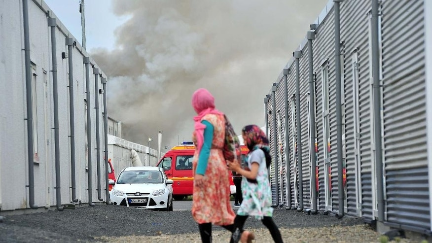 Refugees walk past containers as smoke billows in background in the refugee camp near Kassel, Germany.