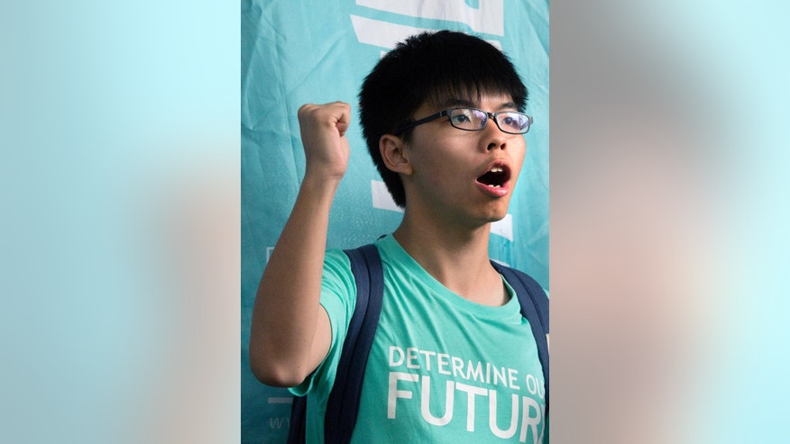 Teen protest leader Joshua Wong shouts slogans outside a magistrate's court in Hong Kong, Monday, Aug. 15, 2016. Three Hong Kong student protest leaders, including Wong, avoided prison time for leading or encouraging an illegal rally that sparked huge pro-democracy street protests two years ago as a magistrate sentenced Wong, Nathan Law and Alex Chow to community service on Monday. (AP Photo/Vincent Yu)