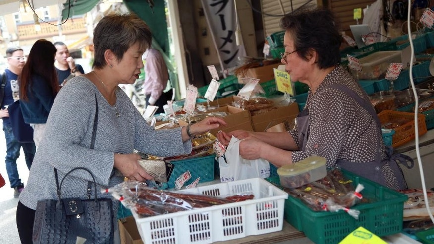 In this June 8, 2016 photo, a shopper buys a product at a dry seafood shop in Tokyo. Japan's economy grew at a slower than forecast 0.2 percent annual rate in the April-June quarter, as the recovery was sapped by weaker exports and business investment, the government said Monday, Aug. 15, 2016. (AP Photo/Eugene Hoshiko)