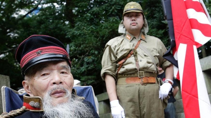 A Japanese veteran, left, and his follower clad in outdated military costumes pose for worshippers taking their photos at Yasukuni Shrine in Tokyo Monday, Aug. 15, 2016. Japan marked the 71st anniversary of the end of World War II. (AP Photo/Shizuo Kambayashi)