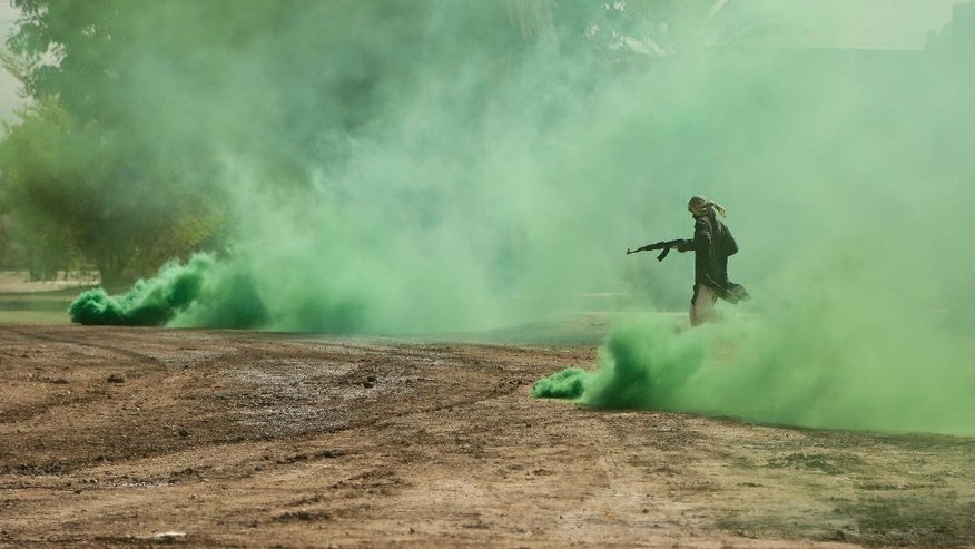 In this Saturday, Aug. 13, 2016 photo, a soldier from the 1st Battalion of the Iraqi Special Operations Forces in the role of an Islamic State militant runs through green smoke during a training exercise to prepare for the operation to re-take Mosul from IS, in Baghdad, Iraq. Iraq's leaders have repeatedly promised that Mosul — which has been in the hands of IS militants for more than two years now — will be retaken this year. (AP Photo/Maya Alleruzzo)