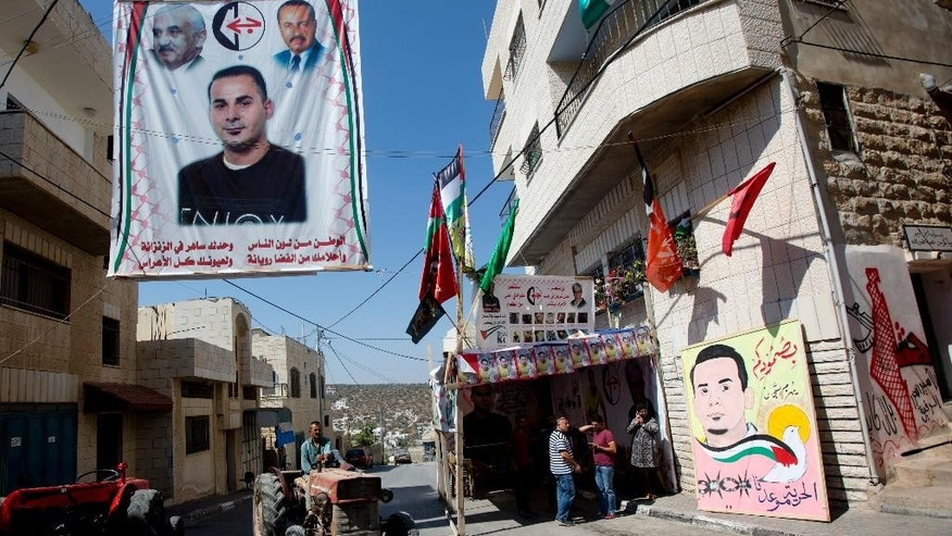 "In this Saturday, Aug. 13, 2016 photo, Palestinians stand by a tent set up in solidarity with Bilal Kayed, 34, in front of his family home in the village of Assira al-Shamaliya near the West Bank city of Nablus. Kayed, 34, started a hunger strike on June 14, after Israel ordered him held for six months without charges, immediately following his completion of a 14-and-a-half-year prison term for shooting at Israeli troops. Poster reads: ""The homeland takes on the color of its people. You are lone in the cell and your dreams are full of light. All the happiness is in your eyes."" Poster on the right reads: ""Your steadfastness defeats the wardens. Freedom is our destiny."" (AP Photo/Majdi Mohammed)"