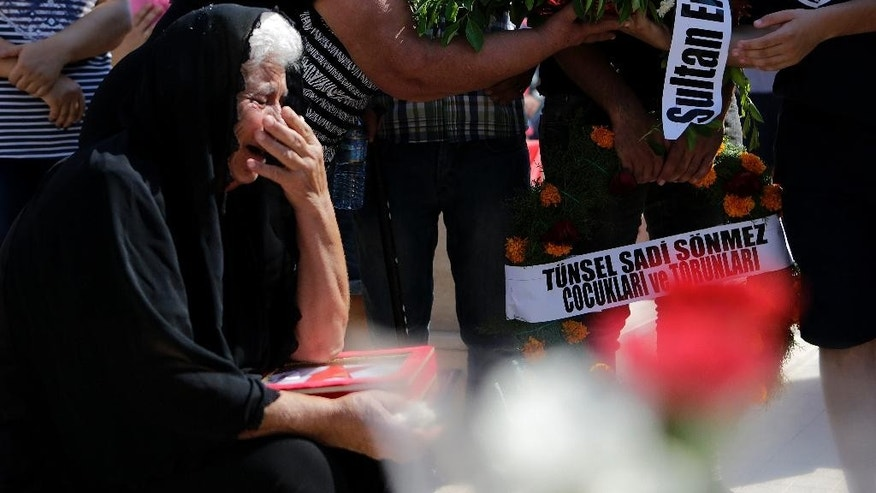 A relative of a missing person mourns over a coffin with his remains, during a funeral service in Taskent village, in the Turkish Cypriot breakaway northern part of the ethnically-divided island of Cyprus, on Monday, Aug. 15, 2016. The remains of 33 Turkish Cypriot villagers who were shot and killed after being taken off two buses during Turkey's 1974 invasion of Cyprus have been laid to rest after they were discovered down a mineshaft four decades later. (AP Photo/Petros Karadjias)