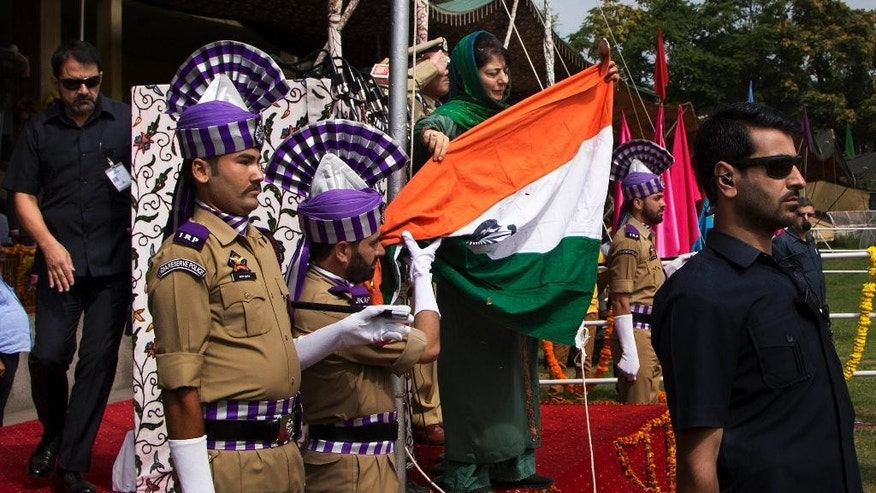 Jammu and Kashmir state Chief Minister Mehbooba Mufti, holds India's national flag after it fell during the unfurling ceremony on India's Independence Day in Srinagar, Indian controlled Kashmir, Monday, Aug. 15, 2016.  Authorities ordered a probe to ascertain if it was a sabotage or negligence after India's national flag fell on the top elected official as she pulled the rope to unfurl the flag at the highly guarded soccer stadium. (AP Photo/Dar Yasin)