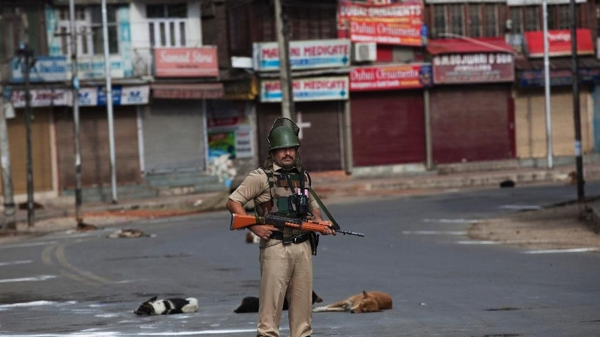 An Indian paramilitary soldier stands guard during curfew on India's Independence Day in Srinagar, Indian controlled Kashmir, Monday, Aug. 15, 2016. The Himalayan region has been under curfew for almost six weeks as the largest street protests in years erupted after Indian troops killed a top rebel leader, and security was tightened further in the week preceding India's independence day. (AP Photo/Dar Yasin)