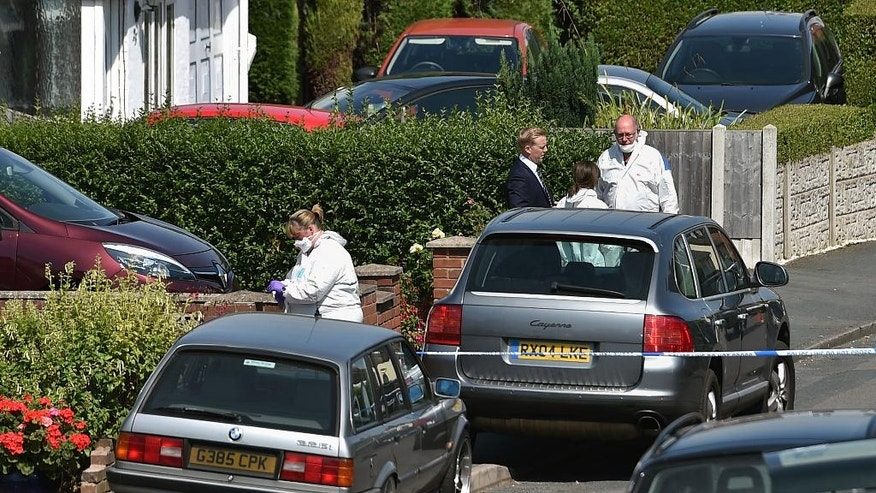 British forensic officers attend the scene where former Aston Villa soccer player Dalian Atkinson died after he was tasered by police early on Monday Aug. 15, 2016, in Telford, England.  Atkinson died after he was shot with a Taser by police, who released a statement saying that police where responding to reports and had concerns for the safety of an individual. (Joe Giddens / PA via AP)