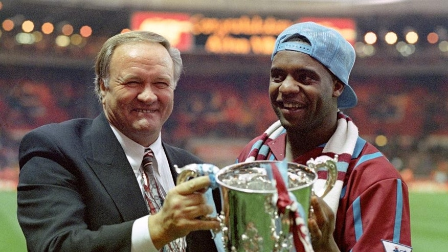 "FILE - This is a March 27, 1994  file photo of Aston Villa manager Ron Atkinson holding the English League Cup with former Aston Villa player Dalian Atkinson at Wembley Stadium in London .  English football club Sheffield Wednesday says Dalian Atkinson  one of its former players has died, following reports he was shot with a Taser by police. Britain's Press Association reported Monday Aug. 15, 2016  that Atkinson died around 90 minutes after a Taser was used on him by police. Local police said in a statement that officers had deployed Taser on a 48-year-old man after responding ""to a report for the concern for the safety of an individual."" (Tony Harris/PA File via AP)"