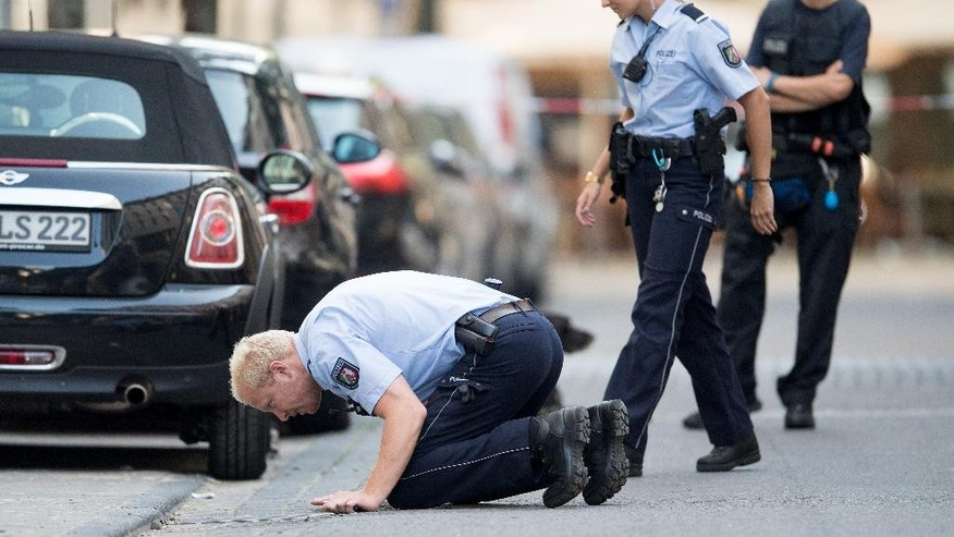 Police search for traces  at the location of  an incident in  Cologne, Germany, Monday Aug. 15, 2016.  Police say one man has been seriously wounded in an early-morning scuffle in the western German city of Cologne. Police spokeswoman Cathrine Maus said a number of callers reported the incident involving several people in downtown Cologne before 4 a.m. She said a man was admitted to the hospital with serious injuries, and there was no immediate information on the nature of his injuries. (Marius Becker/dpa via AP)