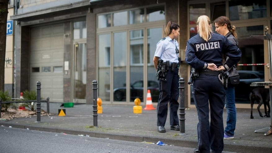 Policewomen standing at the location of an  incident in  Cologne, Germany, Monday Aug. 15, 2016.  Police say one man has been seriously wounded in an early-morning scuffle in the western German city of Cologne. Police spokeswoman Cathrine Maus said a number of callers reported the incident involving several people in downtown Cologne before 4 a.m. She said a man was admitted to the hospital with serious injuries, and there was no immediate information on the nature of his injuries. (Marius Becker/dpa via AP)