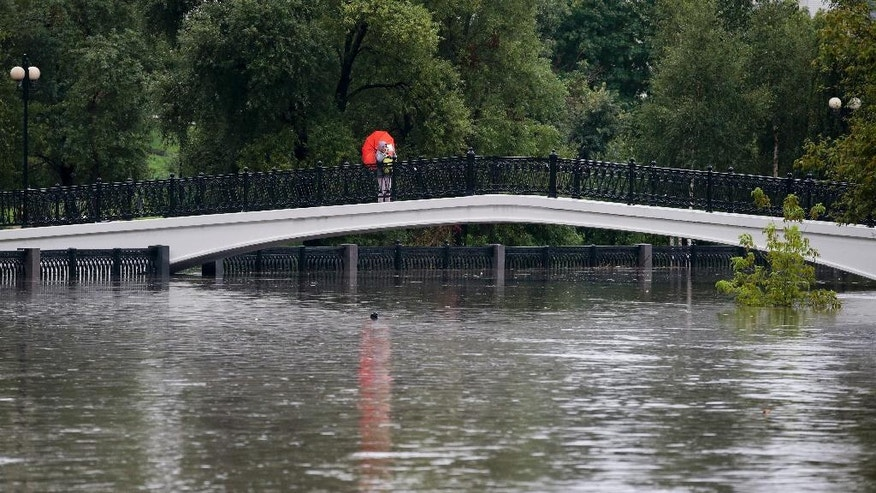 A woman takes a photo with her tablet, standing on a bridge over floodwater in Moscow, Russia, Monday, Aug. 15, 2016, after heavy rain caused a river to burst its banks, flooding streets and trapping people in cars and buses. Russian state news media reported that about 200 people had to be evacuated from stalled vehicles. (AP Photo/Ivan Sekretarev)