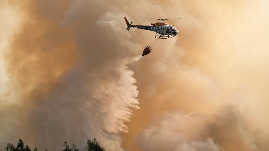 A firefighting helicopter drops its load of water on a forest fire near Santa Comba Dao, northern Portugal, Thursday, Aug. 11 2016. Firefighters in Portugal are battling multiple blazes fed by brush in a hot, dry summer for a sixth straight day. Major fires have also been raging in northwestern Spain and southern France. (AP Photo/Sergio Azenha)