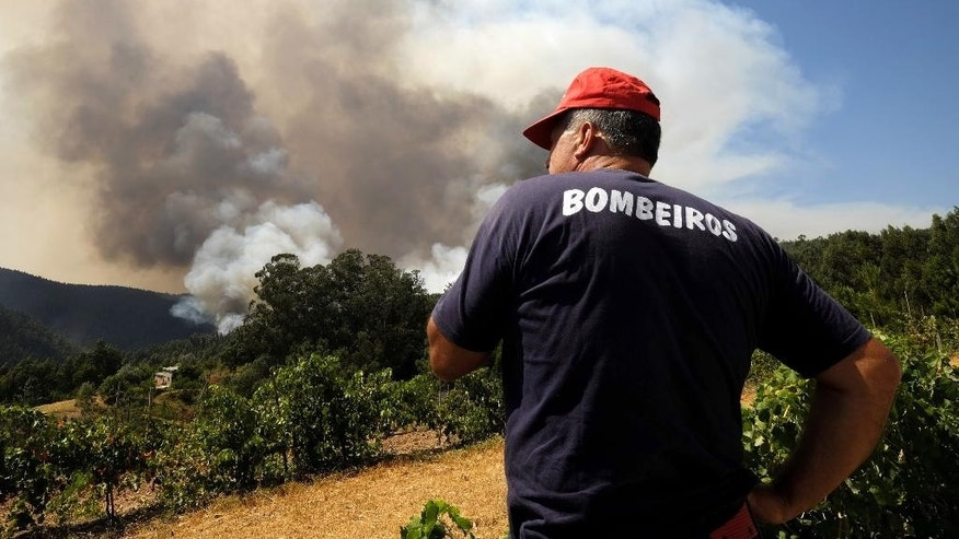 A firefighter watches a fire from their command post in the village of Trezoi near Mortagua, northern Portugal, Thursday, Aug. 11 2016. Firefighters in Portugal are battling multiple blazes fed by brush in a hot, dry summer for a sixth straight day. Major fires have also been raging in northwestern Spain and southern France. (AP Photo/Sergio Azenha)