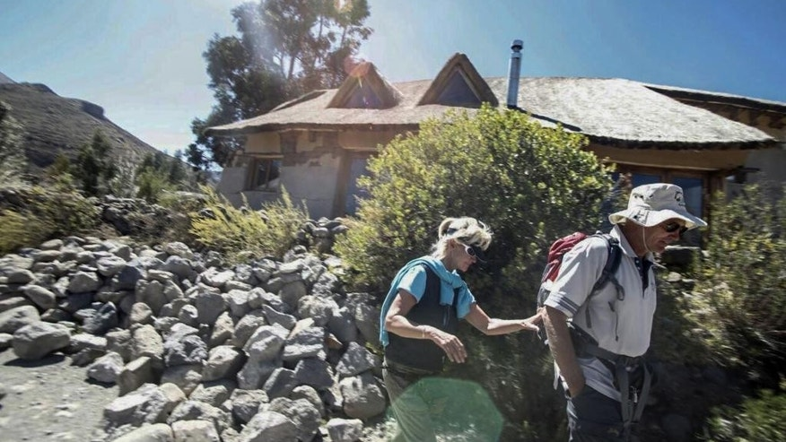 BEST QUALITY AVAILABLE - In this photo provide by government news agency ANDINA, two unidentified tourist walk next a building toppled by an earthquake in Chivay, Peru, Monday, Aug. 15, 2016. A shallow magnitude 5.4 earthquake centered in southern Peru's picturesque Colca Valley killed at least four people, including a 65-year-old U.S. tourist, and left scores injured as it toppled adobe homes. (ANDINA via AP)