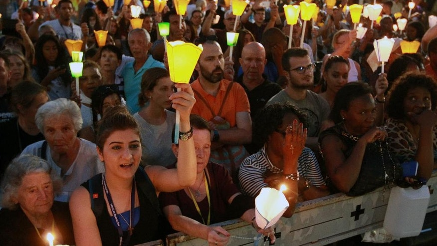 Pilgrims attend a candlelight procession for the Virgin Mary at the sanctuary of Lourdes, southwestern France, Sunday, Aug. 14, 2016. Security measures for Lourdes' biggest annual event, the Feast of the Assumption, has been increased as France, on edge with fears of a new terror attack, continues to cancel festive and sports events for security reasons. (AP Photo/Bob Edme)