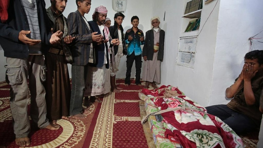 In this July, 24, 2016 photo, mourners pray over the body of 10-year-old Youssef al-Salmi, who was killed when a bomb exploded while he was playing with it near his family's house, in Hasn Faj Attan village, on the mountainous outskirts of Sanaa, Yemen. The village lies near a military base that housed a vast arsenal and Saudi-led airstrikes on the base caused a series of powerful explosions in April 2015. The U.N.'s de-mining coordinator for Yemen, Ahmed Allawi, told The Associated Press that up to 7,800 pieces of unexploded munitions were retrieved from the area, including from Youssef's village. (AP Photo/Hani Mohammed)