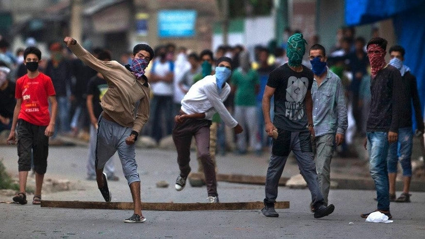 FILE - In this July 30, 2016, file photo, masked Kashmir protesters throw bricks and rocks at Indian policemen during a protest in Srinagar, Indian controlled Kashmir. Tens of thousands of angry youths poured out of their homes in towns and villages across the Himalayan region, hurling rocks and bricks and clashing with Indian troops, after Indian troops killed a charismatic commander of Kashmir's biggest rebel group. A strict curfew and a series of communications blackouts since then have failed to stop the protesters, who are seeking an end to Indian rule in Kashmir. (AP Photo/Dar Yasin, File)