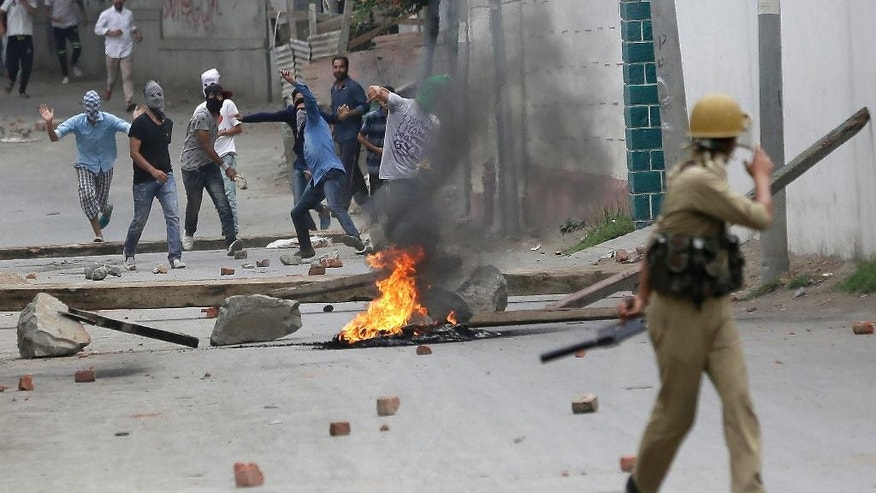 FILE - In this Aug. 10, 2016, file photo, masked Kashmiri protesters throw stones at police in Srinagar, Indian-controlled Kashmir. Tens of thousands of angry youths poured out of their homes in towns and villages across the Himalayan region, hurling rocks and bricks and clashing with Indian troops, after Indian troops killed a charismatic commander of Kashmir's biggest rebel group in early July 2016. A strict curfew and a series of communications blackouts since then have failed to stop the protesters, who are seeking an end to Indian rule in Kashmir. (AP Photo/Mukhtar Khan, File)