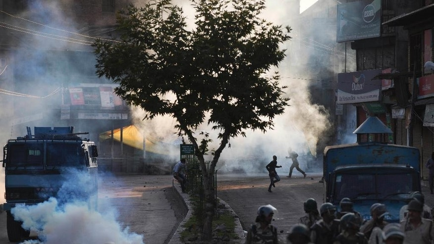 FILE - In this Aug. 8, 2016, file photo, Kashmiri Muslim protesters run for cover from plumes of tear gas as Indian paramilitary soldiers walk back towards their base camp after a day-long curfew in Srinagar, Indian controlled Kashmir. Tens of thousands of angry youths poured out of their homes in towns and villages across the Himalayan region, hurling rocks and bricks and clashing with Indian troops, after Indian troops killed a charismatic commander of Kashmir's biggest rebel group in early July 2016. A strict curfew and a series of communications blackouts since then have failed to stop the protesters, who are seeking an end to Indian rule in Kashmir. (AP Photo/Dar Yasin, File)