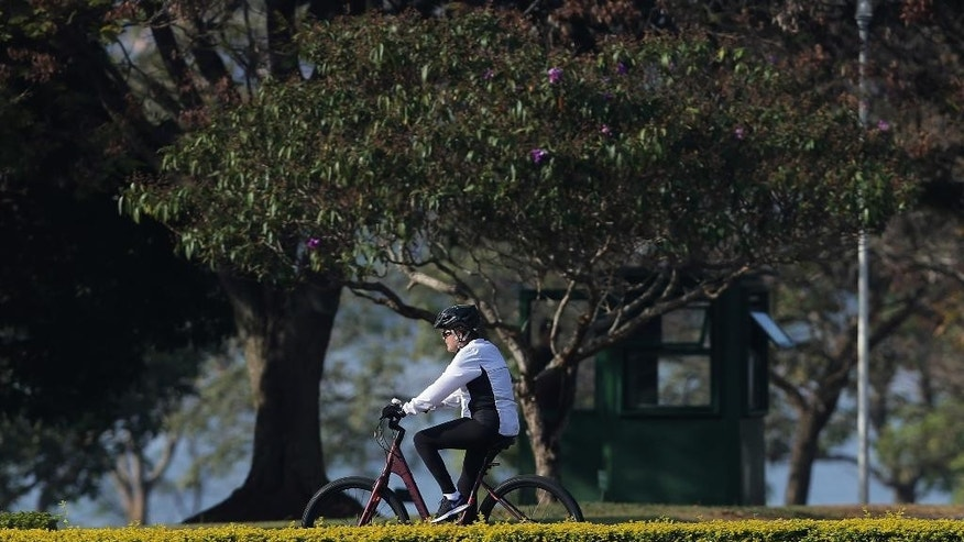 Brazil's suspended President Dilma Rousseff rides her bicycle in front of the official residence Alvorada Palace, in Brasilia, Brazil, Monday morning, Aug. 15, 2016. Brazil's Supreme Court announced Friday, Aug. 12, that the final impeachment trial of the suspended leader will be held on Aug. 25. (AP Photo/Eraldo Peres)