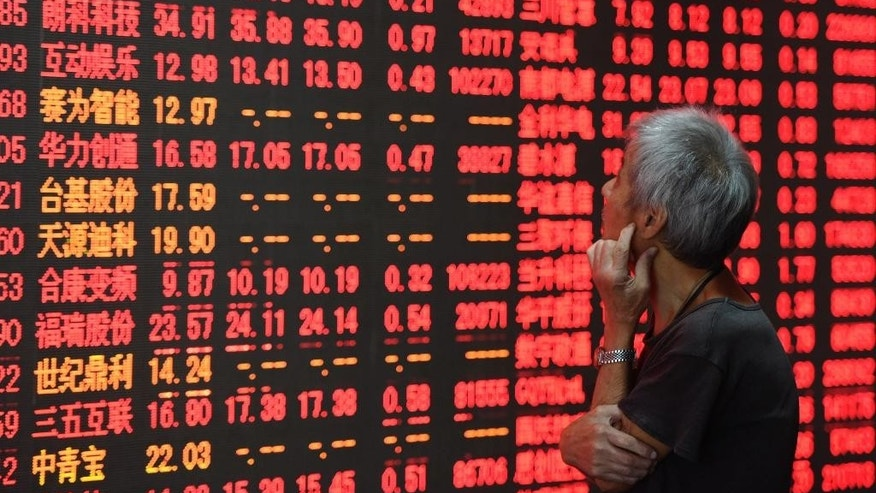 In this Monday, Aug. 15, 2016 photo released by Xinhua News Agency, an investor stares at a stock price board at a stock trading hall in Hangzhou, capital of east China's Zhejiang Province. China's Cabinet approved a long-awaited initiative Tuesday, Aug. 16, that will give foreign investors more access to Chinese stocks by linking stock exchanges in Hong Kong and the mainland city of Shenzhen. (Long Wei/Xinhua via AP)